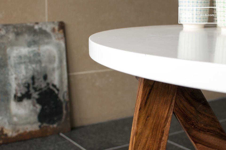 Die weiss glänzende Tischplatte liegt auf den Beinen aus massivem Holz auf